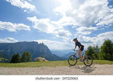 ALPE DI SIUSI, ITALY-JULY 04, 2009: mountain biker woman cycling on mountain path in a summer sunny day, in the Dolomites Alpe di Siusi.