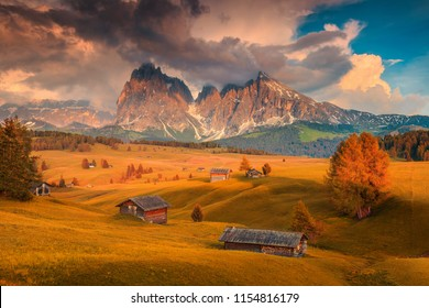 Alpe di Siusi - Seiser Alm with Sassolungo - Langkofel mountain group in background at sunset. Colorful autumn landscape and wooden chalets in Dolomites, Trentino Alto Adige, Italy, Europe