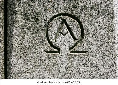 Alpha omega symbol carved in grey granite stone