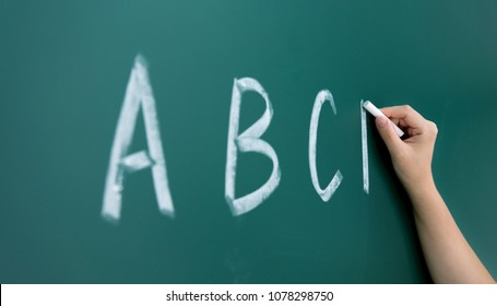 Alphabet abc hand chalk on blackboard