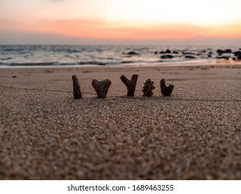 alphabet by corals on the beach with the sea as a background