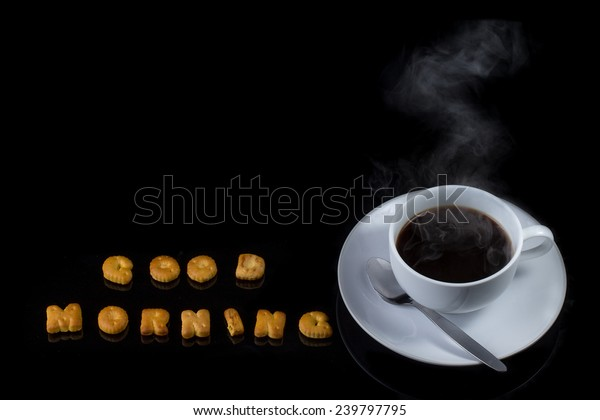 Alphabet cracker with cup of coffee with steam