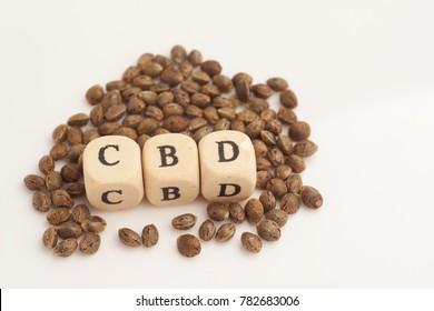 Alphabet cubes with cannabis seeds on white background CBD