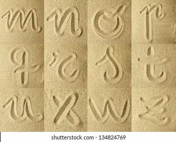 alphabet handwritten in the sand