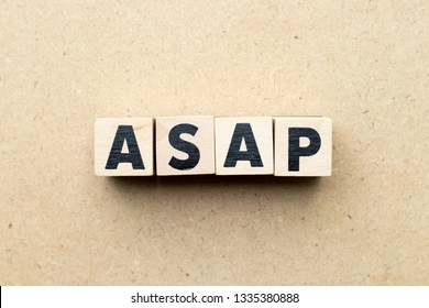 Alphabet letter block in word ASAP (Abbreviation of as soon as possible) on wood background