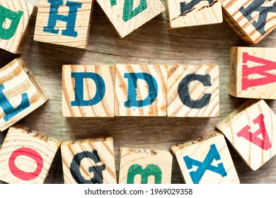 Alphabet letter block in word DDC (Abbreviation of Division of disease control,  Direct digital control, Display Data Channel or Dewey Decimal Classification) with another on wood background