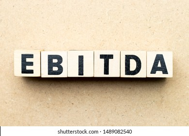 Alphabet letter block in word EBITDA (abbreviation of earnings before interest, taxes, depreciation and amortization) on wood background