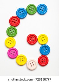 Alphabet letter formed from colorful sewing buttons. Isolated on white background.