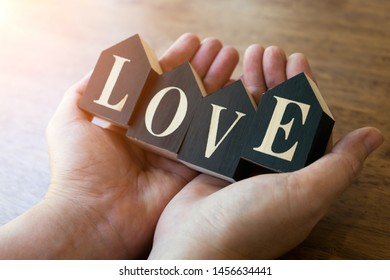 Alphabet letter wooden blocks with words LOVE in hands with lighting,love for Valentine's day or wedding for lover.Keeping love with our hands concept.