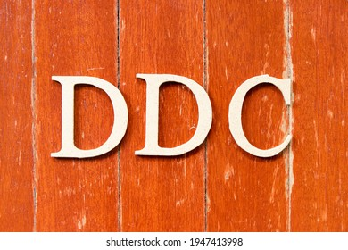 Alphabet letter in word DDC (Abbreviation of Division of disease control,  Direct digital control, Display Data Channel or Dewey Decimal Classification) on old red color wood plate background