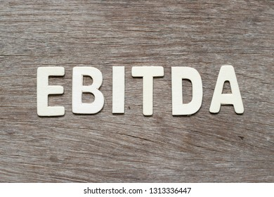 Alphabet letter in word EBITDA (abbreviation of earnings before interest, taxes, depreciation and amortization) on wood background