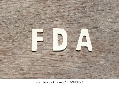 Alphabet letter in word FDA (abbreviation of food and drug administration) on wood background