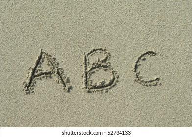 alphabet letters a b c handwritten in sand on beach