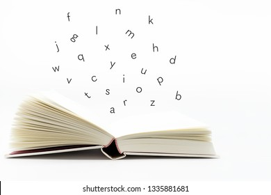 Alphabet letters fallling on open book on white background