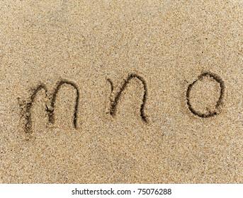 alphabet letters m n o handwritten in sand on beach