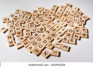 Alphabet letters on wooden scrabble pieces scattered randomly on white background