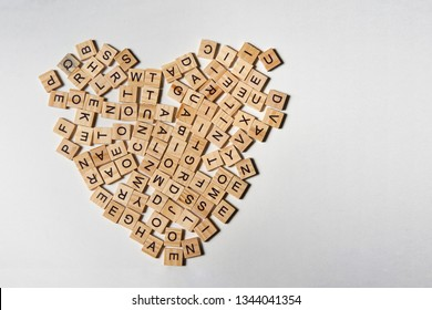 Alphabet letters on wooden square pieces forming heart shape on white background
