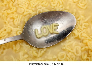 "Alphabet letters in spoon spell out ""Love"". Alphabet Soup Pasta. Closeup."