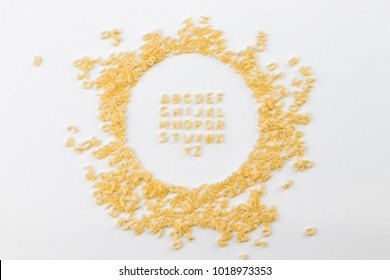 Alphabet made of macaroni letters isolated on white background.