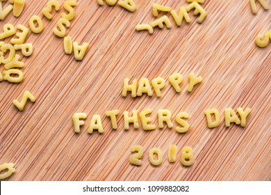 Alphabet pasta forming the text Happy Fathers Day 2018, wood background