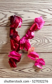 Alphabet of rose petals - K letter laid out from the petals of red roses and pink flowers on a wooden light background