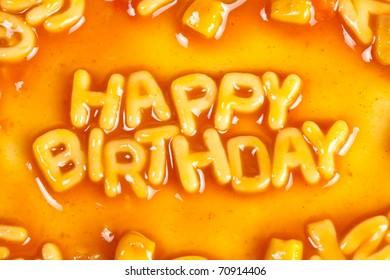 Alphabet shaped pasta forming HAPPY BIRTHDAY in tomato sauce