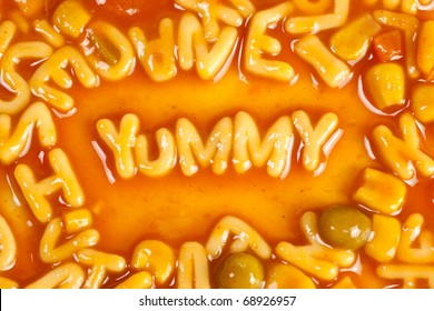 Alphabet shaped pasta forming the word YUMMY in tomato sauce