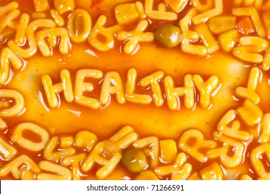 Alphabet shaped pasta forming the word HEALTHY in tomato sauce