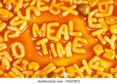 Alphabet shaped pasta forming the word MEALTIME in tomato sauce