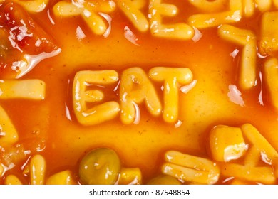 Alphabet shaped pasta forming the word EAT in tomato sauce