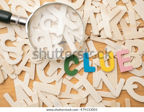 An alphabet spell clue on top of random alphabet background,shot from top