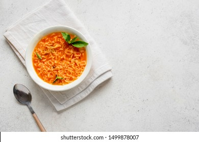 Alphabet Tomato Soup. Vegetable soup with alphabet pasta on white background, copy space, top view. Minestrone soup for kids.