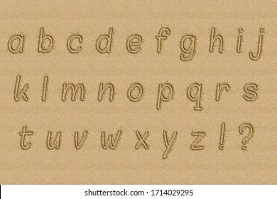 Alphabet written on the shore of a beach