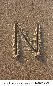 Alphabet's letter N handwritten in sand on the beach, at sunrise.