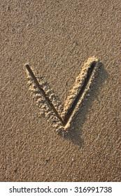 Alphabet's letter V handwritten in sand on the beach, at sunrise.