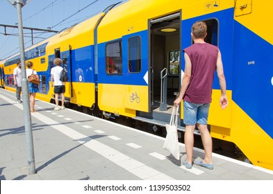Alphen aan den Rijn, Netherlands, 21-07-2018: people waiting for the NS train to open its doors on a summer day in the Netherlands