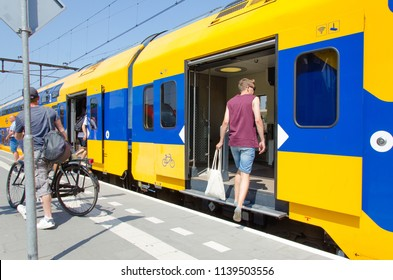 Alphen aan den Rijn, Netherlands, 21-07-2018: people entering into a NS train on a summer day in the Netherlands