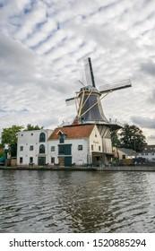 Alphen aan den Rijn, Netherlands - September 30th 2019: Scenic view of classic production windmill 'De Eendracht' along the river 'Oude Rijn'.