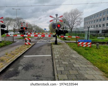 Alphen aan den Rijn, The Netherlands - May 15 2021: Dutch railroad crossing, red traffic lights and stop signs. Warning there is a train coming