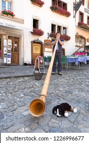 An Alphorn player in the Swiss village of Gruyères, in the canton of Fribourg, Switzerland.The town and region are famous for their Swiss Cheese called Gruyere.