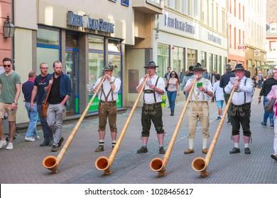 Alphorn player in traditional Bavarian costumes performing on the street of Heidelberg at the fall folk festival. Heidelberg, Germany - September 24 2016.