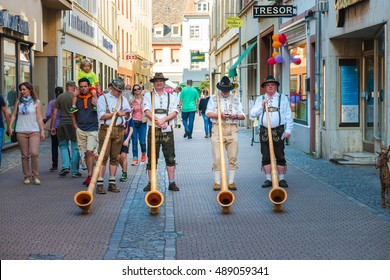 Alphorn player in traditional Bavarian costumes performing on the street of Heidelberg at the fall folk festival - September 24 2016, Heidelberg, Germany.