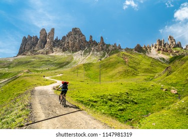 Alpine activities in Dolomites,Italy. Mountainbiking uphill on the Mountain Road in Dolomites Mountains. Rocky Mountains Ridge in the background. Cycling with bikes on track, Cortina d'Ampezzo