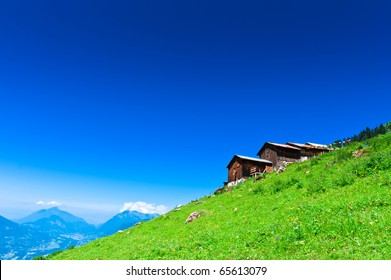 Alpine chalets on green mountain slope under blue sky. French Apls.