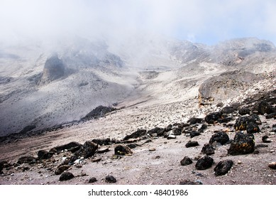 Alpine desert - arid and barren - shrouded in clouds with the blue sky beyond peaking through. Taken on the slopes of Mt kilimanjaro, Tanzania
