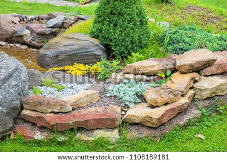 Alpine Garden With Bridge And Small Pond With Water