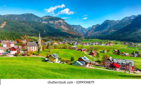 Alpine green fields and traditional wooden houses view of the Gosau village at autumn sunny day. Location: resort village Gosau Salzkammergut region, Gosau Valley in Upper Austria, Alps. Europe.