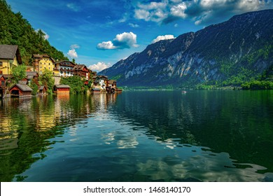 Alpine houses on the shore of a crystal clear blue and green lake.