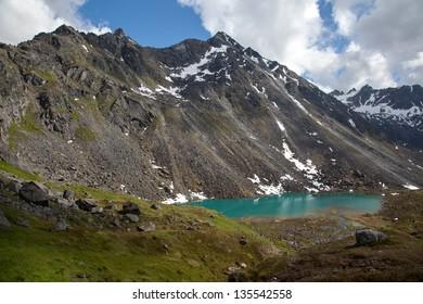 Alpine lake at base of rugged mountain