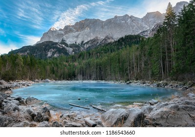 Alpine lake with blue frozen water, surrounded by fir forest and the Alps mountains, near the Eibsee lake, in Bavaria, Germany.